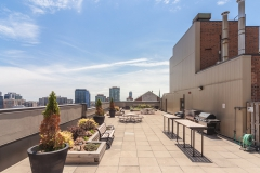 Rooftop terrace area with eating area and bbqs, blue sky and cityscape behind
